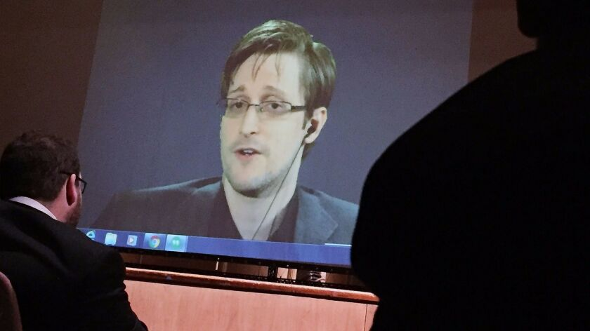 Former National Security Agency contractor Edward Snowden, center speaks via video conference to peo