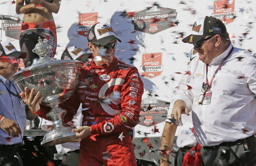 Scott Dixon, of New Zealand, holds the Astor Cup after winning the IndyCar Grand Prix of Sonoma auto race and IndyCar championship as team owner Chip Ganassi, right, looks on Sunday, Aug. 30, 2015, in Sonoma, Calif. (AP Photo/Eric Risberg)