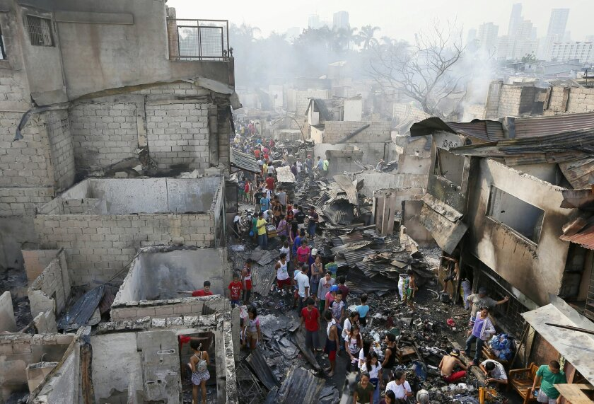 Fire survivors sift through the debris, a day after a huge fire razed an informal settlers' community in suburban Mandaluyong city, east of Manila, Philippines Thursday, Nov. 26, 2015. Fire officials say no casualties were reported but about 800 houses were razed and thousands of informal settlers were rendered homeless. (AP Photo/Bullit Marquez)