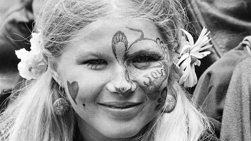 Judy Smith, sporting face paint and flowers in her hair, smiles as she and others gather in San Francisco's Golden Gate Park in June, 1967.