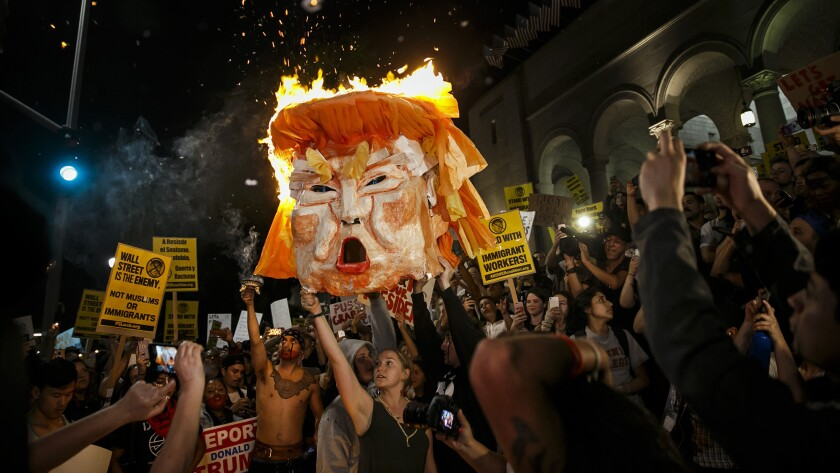 Protesters burn an effigy of Donald Trump outside Los Angeles City Hall on Wednesday.