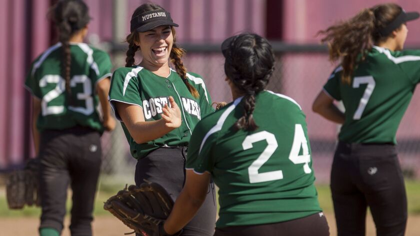 Costa Mesa's Haley Sheffner laushgs with Brandy Rodriguez (24) during an Orange Coast League game ag