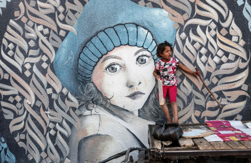 A Palestinian girl stands on donkey cart next to wall painting at a UN school where people are taking shelter in Gaza city.