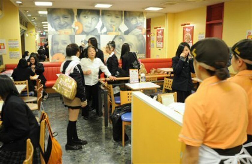 High school girls and other customers react at a donut parlor in Iwaki, Fukushima Prefecture, Friday, Dec. 7, 2012 as a strong earthquake strikes off the coast of northeastern Japan. It is the same region that was hit by a massive earthquake and tsunami last year. (AP Photo/Kyodo News) JAPAN OUT, MANDATORY CREDIT, NO LICENSING IN CHINA, FRANCE, HONG KONG, JAPAN AND SOUTH KOREA
