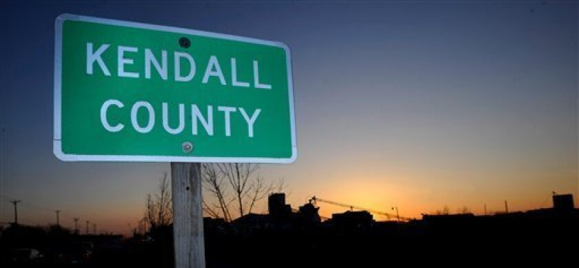 FILE - This March 19, 2008, file photo shows a Kendall County street sign in Oswego, Ill., about 50 miles west of Chicago. The nation's No. 1 fastest-growing county from 2000 to 2010, Kendall was part of an exurban wave in the heady 2000s that more than doubled Kendall's population. Now Census estimates as of July 2011 highlight a shift in population trends, following an extended housing bust and renewed spike in oil prices; outlying suburbs are now seeing their growth fizzle to historic lows, halting American city dwellers' decades-long exodus to sprawling homes in distant towns. (AP Photo/Paul Beaty, File)