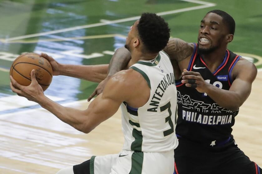 Milwaukee Bucks' Giannis Antetokounmpo is fouled as he drives to the basket against Philadelphia 76ers' Shake Milton during the second half of an NBA basketball game Thursday, April 22, 2021, in Milwaukee. (AP Photo/Aaron Gash)