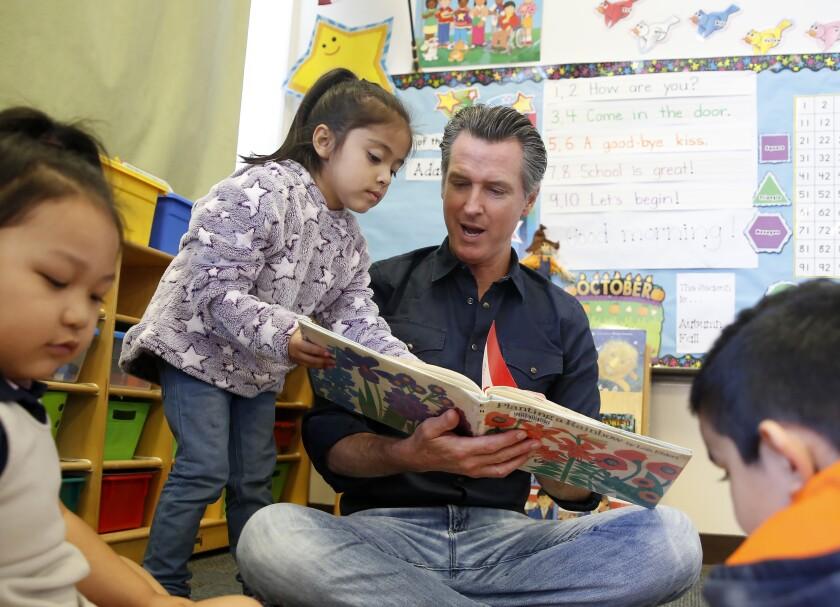 California Gov. Gavin Newsom and kindergartner Priscilla Ramirez read a book during his visit to the Ethel I. Baker Elementary School in Sacramento on Monday.