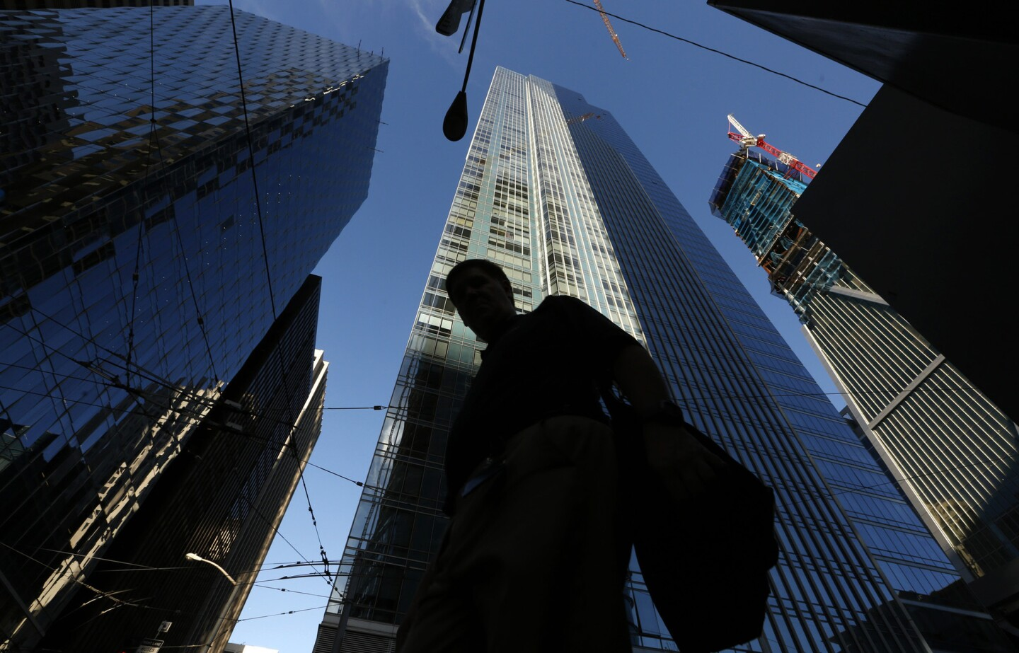 A pedestrian walks past the luxury Millennium Tower, a 58-story high rise in San Francisco.
