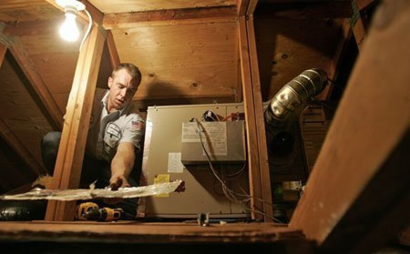 Crouched in a home's attic, Brian Dorney of Bill Howe Plumbing worked on an air-conditioning unit. Howe's general manager says even a slight increase in workers' compensation rates could cause the company to trim its budget or raise its prices. (Howard Lipin / Union-Tribune)