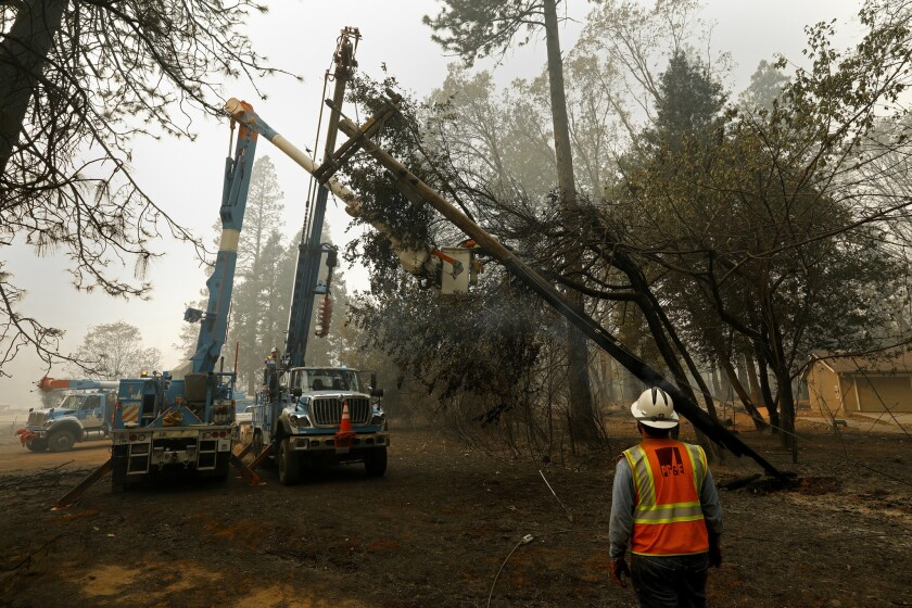 PG&E workers take down damaged power lines near Pulga in the wake of the Paradise fire.