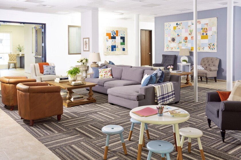 The living room of the San Fernando Valley Rescue Mission features comfy oversized furniture including a sectional from Sears, coffee table, side chairs and lamps from Lamps Plus, handmade quilts by Crafting Community and a child's play table from Serena & Lily.