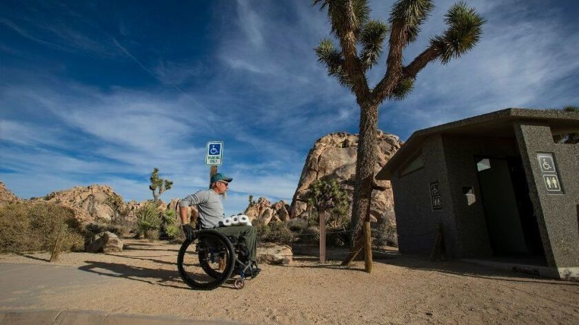 Rand Abbott of Joshua Tree, Calif., carries extra toilet paper to refill a bathroom stall after cleaning it in Joshua Tree National Park on Jan. 8.