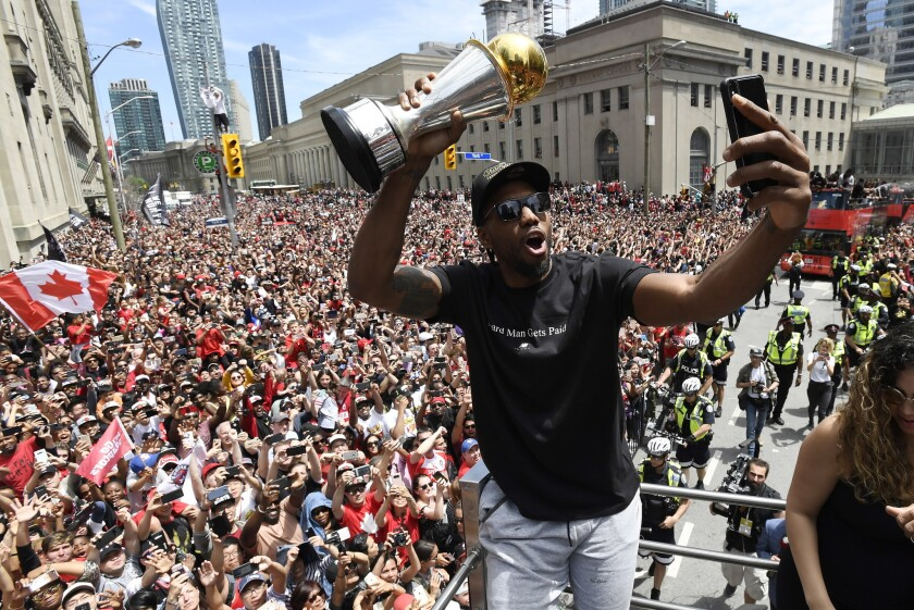 Toronto Raptors forward Kawhi Leonard takes a selfie holding his playoffs MVP trophy during the NBA