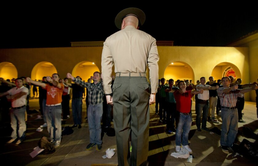 A Marine drill instructor speaks to new recruits in formation after they arrived by bus. A new military policy bill would integrate women into the all-male San Diego Marine Corps boot camp.