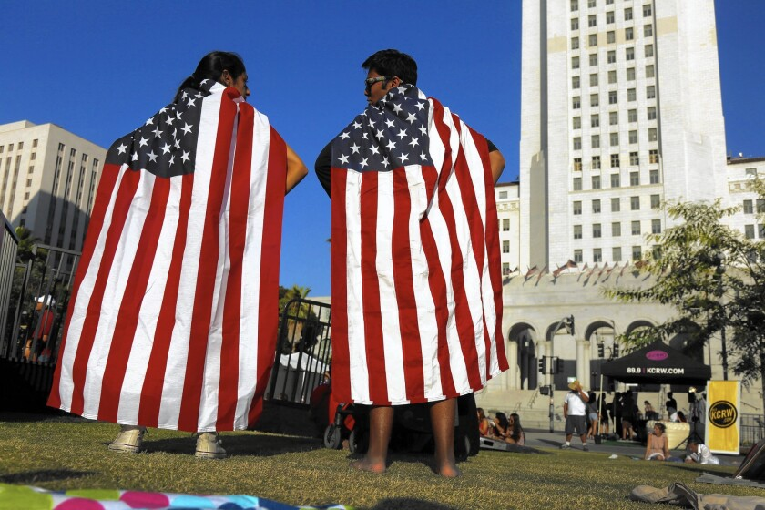 Hijab Gulwani, 18, of Los Angeles and Zain Delawalla, 16, of Santa Monica pose for a friend while wearing American flags at the third annual Fourth of July Block Party at Grand Park in downtown L.A.