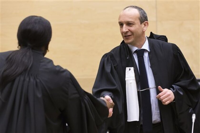 Emmanuel Altit, the defence counsel for former Ivory Coast President Laurent Gbagbo, right, shakes hands with International Criminal Court (ICC) prosecutor Fatou Bensouda, left, prior to the start of a confirmation of charges hearing at the ICC in The Hague, Netherlands, Tuesday Feb. 19, 2013. ICC