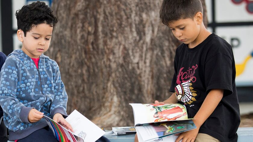 Kindergartners Marco Ceja, left, and Jose Flores look at their new books during a book giveaway pres