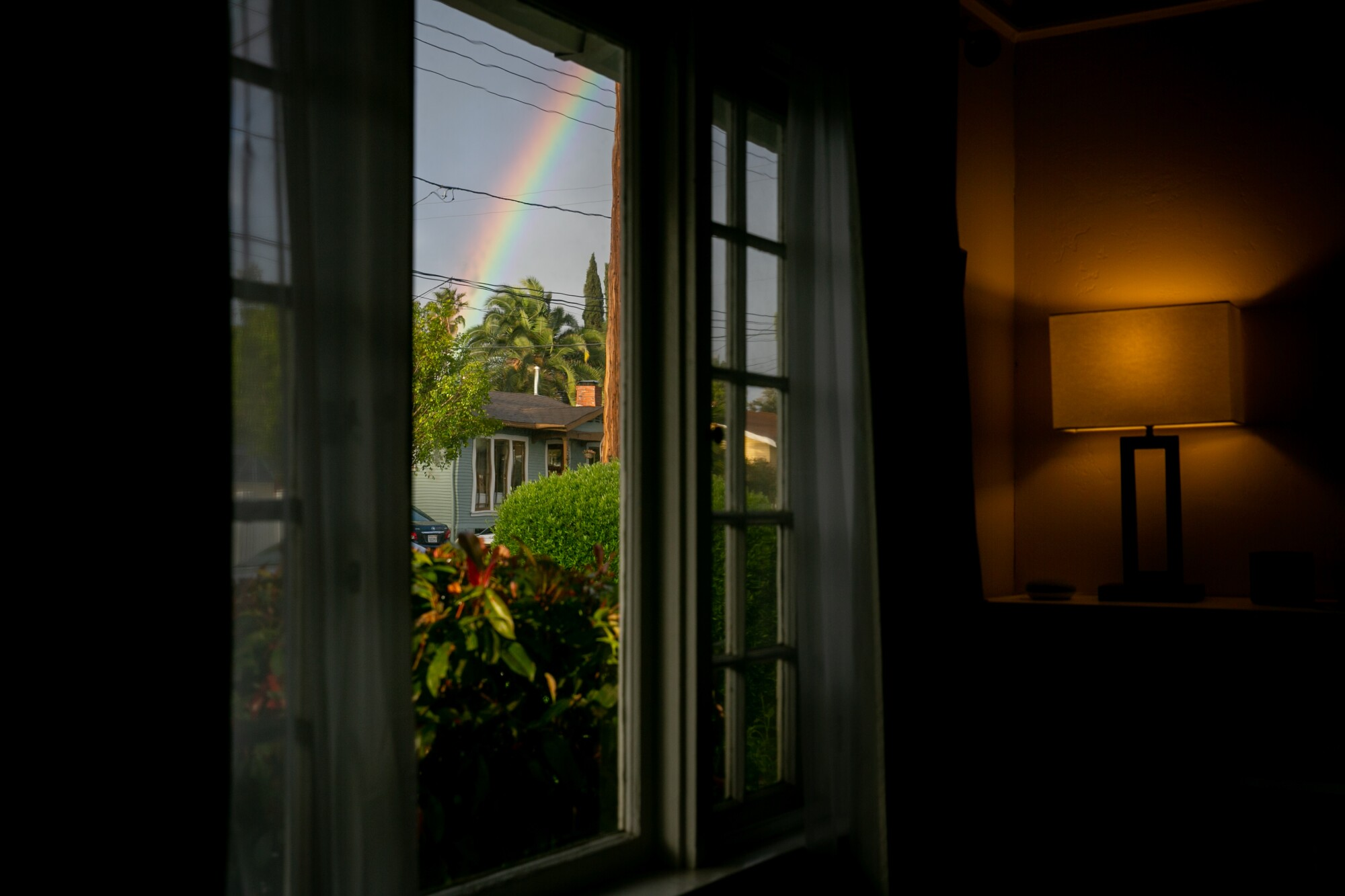 A rainbow peeks through the clouds after a rainfall as seen from the photographer's home on March 26, 2020 in San Diego, California. Air quality has been consistently good in San Diego as businesses shuttered and vehicles stay off the road.