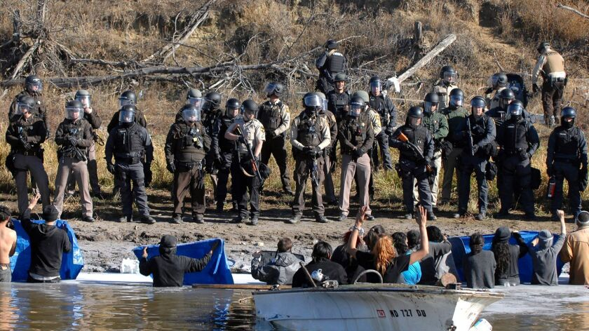 Dakota Access pipeline protesters stand waist deep in the Cantapeta Creek as officers in riot gear  standing on the shoreline.