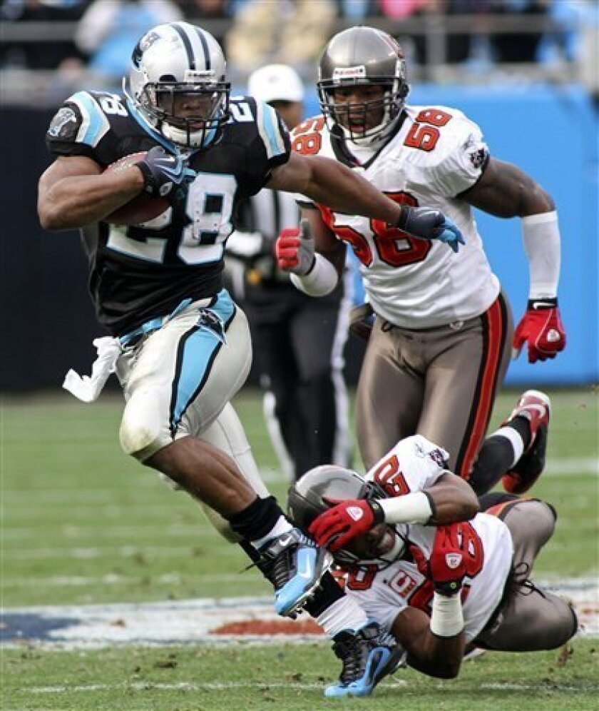 Carolina Panthers' Jonathan Stewart (28) runs past Tampa Bay Buccaneers' Ronde Barber (20) and Quincy Black (58) in the first half of an NFL football game in Charlotte, N.C., Sunday, Dec. 6, 2009. (AP Photo/Rick Havner)