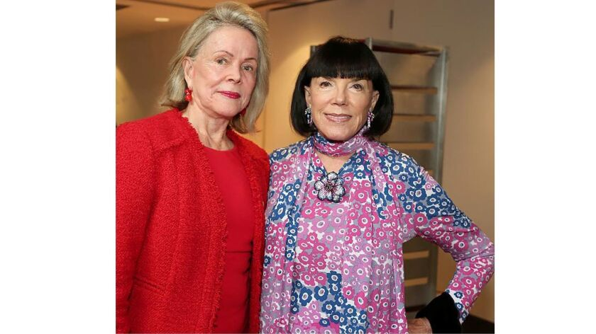 Photographer Kitty Keck, left, and watercolorist Gayle Roski greet guests at the Jan. 13 art recepti