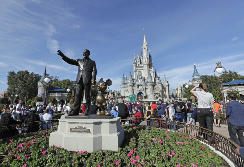 FILE - In this Jan. 9, 2019, file photo, theme park guests walk near a statue of Walt Disney and Mickey Mouse in front of the Cinderella castle in the Magic Kingdom at Walt Disney World in Lake Buena Vista, Fla. Disney said Tuesday, Sept. 24, that plant-based meals would be available at all of its restaurants and quick-meal hubs at Walt Disney World in Florida and Disneyland Resort in California.(AP Photo/John Raoux, File)