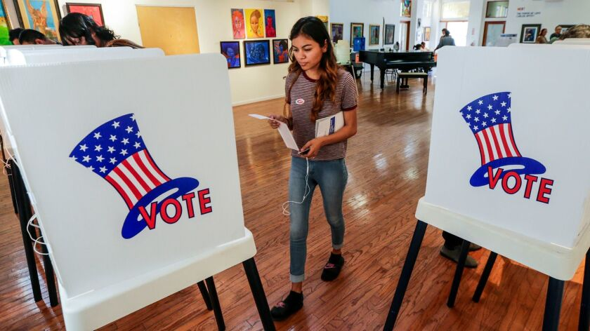 First-time voter Maryjane Medina, 18, approaches a polling booth to cast her vote at the Watts Towers Arts Center. Lawmakers want voters in 2018 to approve a $450-million bond to upgrade voting equipment.