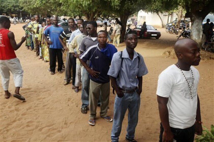 Togolese queue to cast their votes for president, outside a polling station in Lome, Togo, Thursday, March 4, 2010. Polls were open Thursday in the African nation of Togo, as the son of a long-ruling dictator seeks re-election to the presidency, facing six opposition candidates. (AP Photo/Sunday Alamba)