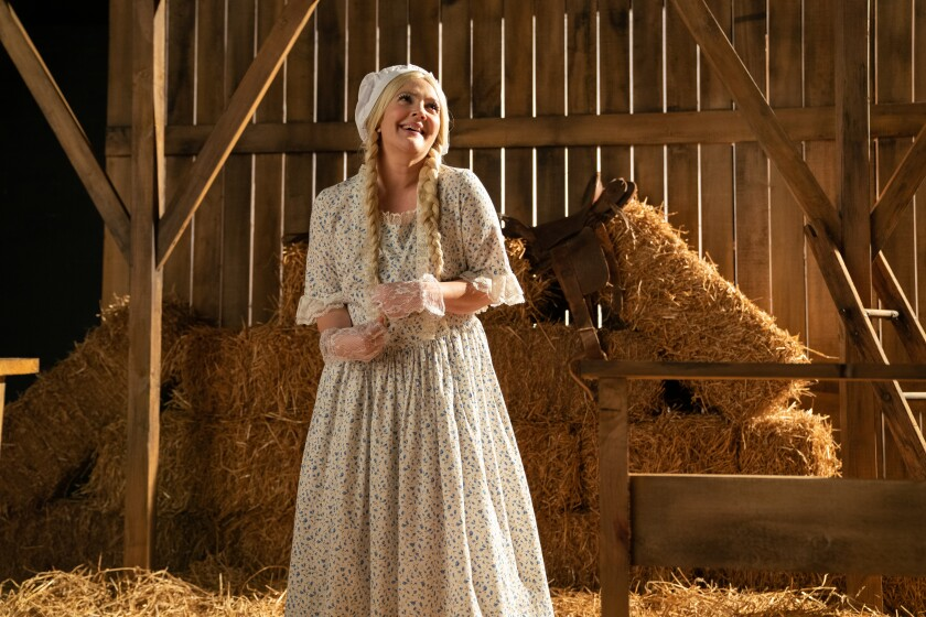"""Drew Barrymore stands amid hay bales in a barn, wearing a long dress, gloves and bonnet, in """"The Stand In."""""""