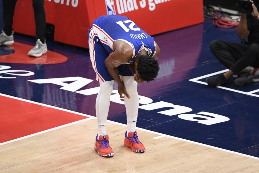 Philadelphia 76ers center Joel Embiid reacts after sustaining a knee injury during the first quarter.