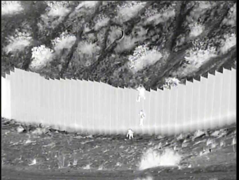This Tuesday, March 30, 2021 photo taken from night video provided by the U.S. Customs and Border Protection shows a smuggler dropping children from the top of border barrier in Santa Teresa, N.M. Video released Wednesday, March 31 by federal authorities show the two Ecuadoran children being abandoned by smugglers after they were dropped over a 14-foot-high barrier along the U.S.-Mexico border. Authorities said Santa Teresa border agents were able to find the 3- and 5-year-old sisters after being directed by the camera operator to the remote location in New Mexico, just west of El Paso, Texas. The girls were alert but were taken to a hospital to be checked out and cleared. (U.S. Customs and Border Protection via AP)