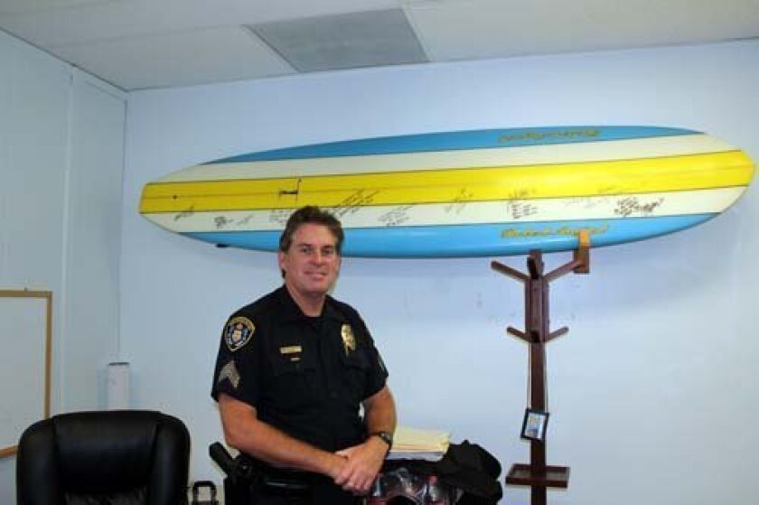Lt. Paul Rorrison has put his name on the surfboard signifying his new role. Photo: Dave Schwab