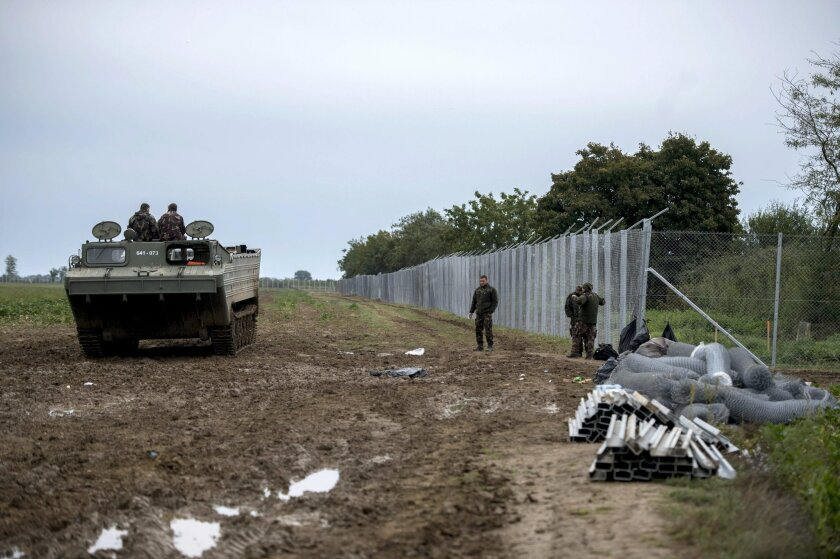 Hungarian soldiers go in a PTS amphibious transport vehicle near the border crossing between Hungary and Croatia at Beremend, 237 kms south of Budapest, Hungary, Monday, Sept. 28, 2015. (Tamas Soki/MTI via AP)