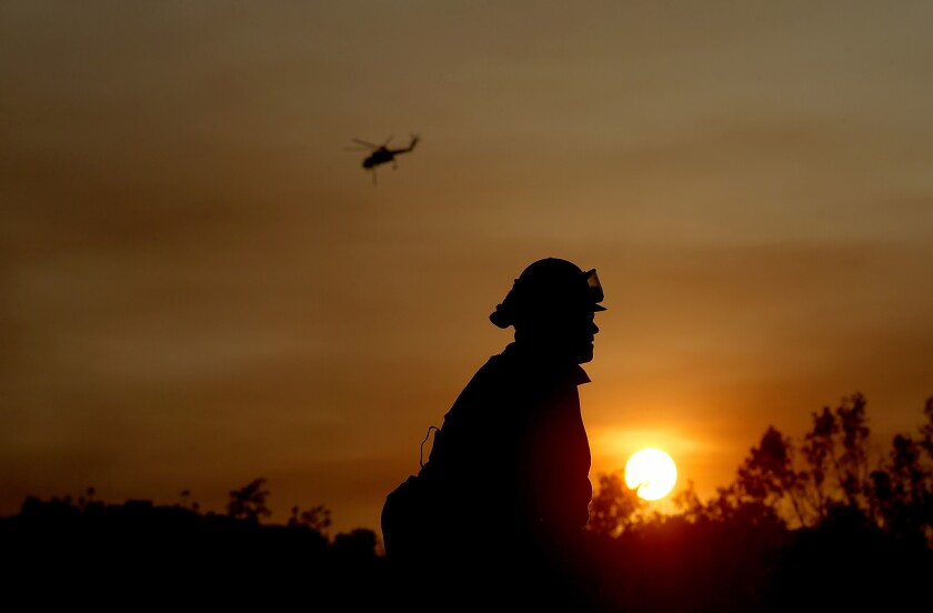 The sun sets behind a firefighter working along Country Club Drive in Escondido on Thursday evening as wildfires continued to burn in San Diego County.