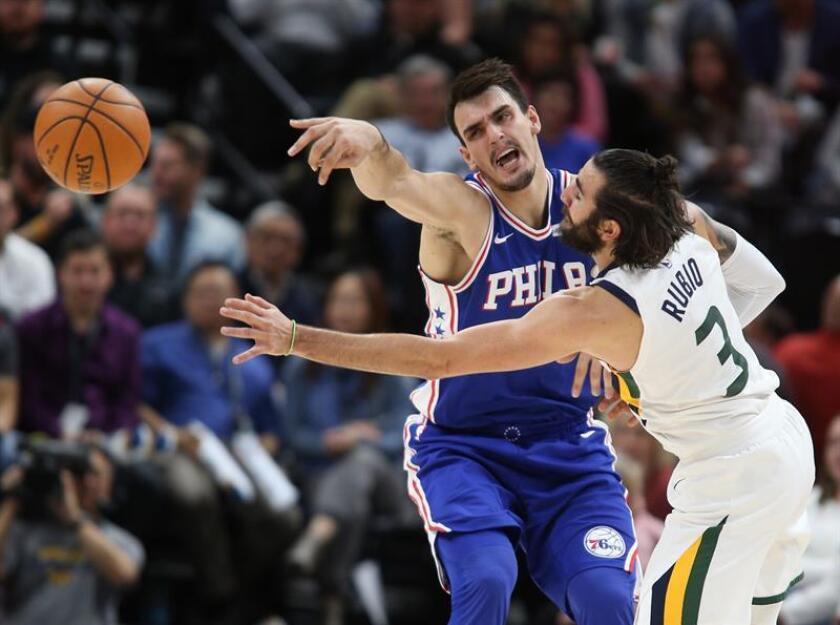 Ricky Rubio (d), base español de los Jazz de Utah, fue registrado este martes al intentar bloquear un pase de Dario Saric (i), ala pívot croata de los Sixers de Filadelfia, durante un partido de la NBA, en el Energy Solutions Arena de Salt Lake City (Utah, EE.UU.). EFE