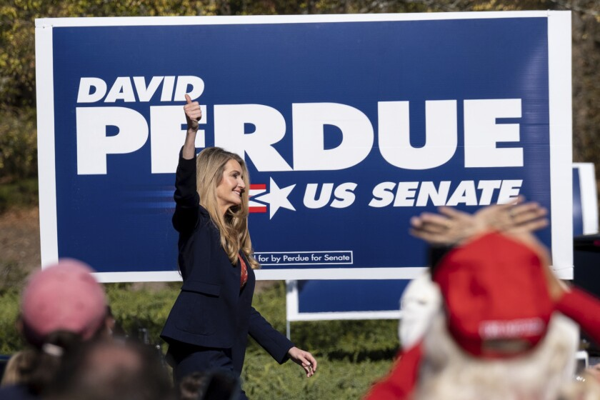Sen. Kelly Loeffler takes the stage at a rally with a David Purdue for U.S. Senate sign behind her.