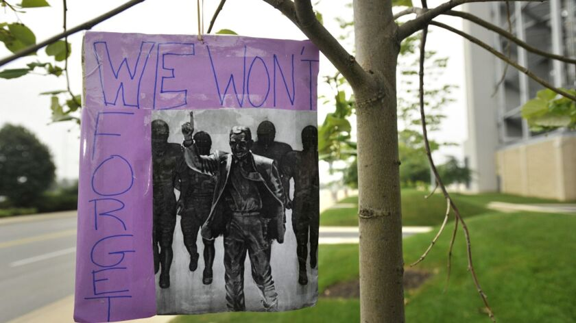 "A sign reading ""We won't forget"" hangs from a tree at the site where former Penn State college footb"