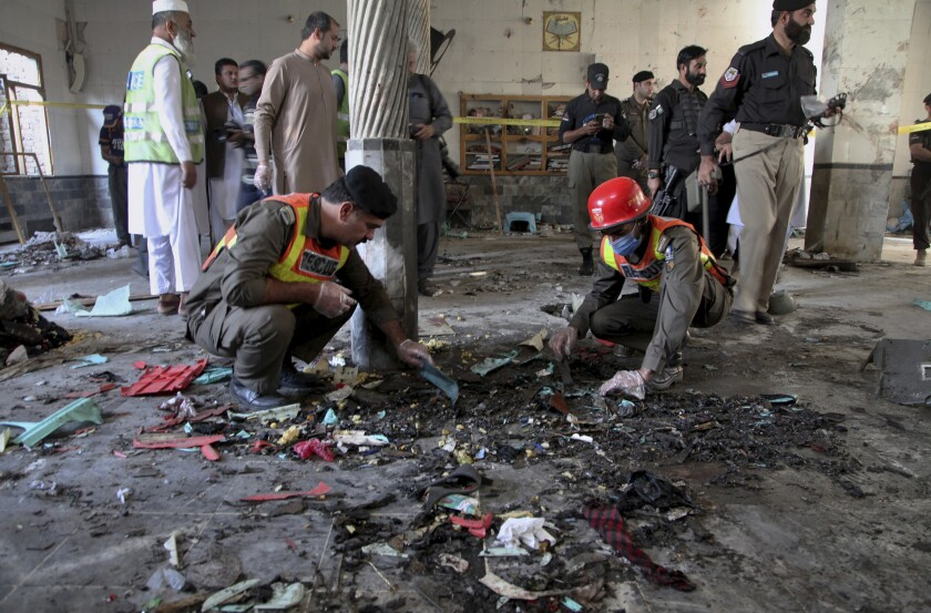 Rescue workers and police officers examine an Islamic school in Peshawar, Pakistan, that was hit by a powerful bomb Tuesday.