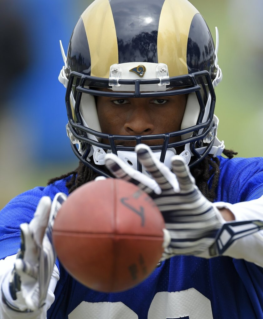 FILE - In this June 1, 2016, file photo, Los Angeles Rams running back Todd Gurley catches passes from a machine during NFL football practice in Oxnard, Calif.  In the first few months since the Rams went Hollywood, Todd Gurley has already landed commercials, endorsements and national exposure. The