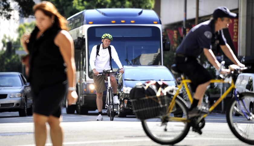 A cyclist uses a bike lane in downtown Los Angeles on Aug. 11. The L.A. City Council recently approved a sweeping transportation plan that calls for the addition of hundreds of miles of new bicycle lanes, bus-only lanes and other road redesigns over the next 20 years.