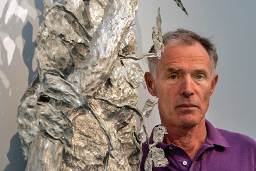 Robert Lobe with a work made from hammered aluminum and hammered galvanized iron.