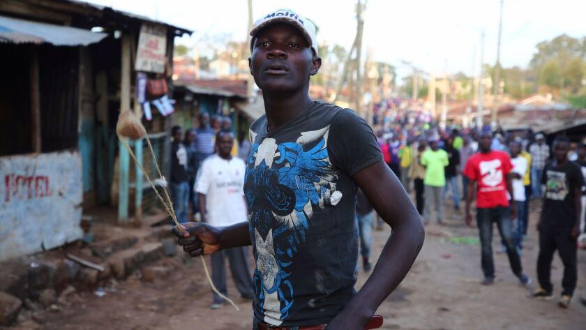 An opposition supporter in Kenya holds a sling during clashes with riot police after Uhuru Kenyatta was declared president by the Independent Electoral and Boundaries Commission.