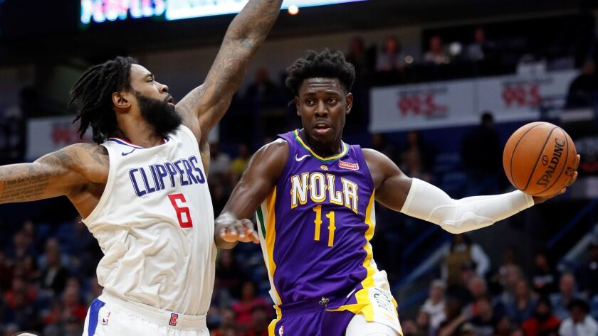 New Orleans Pelicans guard Jrue Holiday passes around Clippers center DeAndre Jordan on Sunday at the Smoothie King Center.