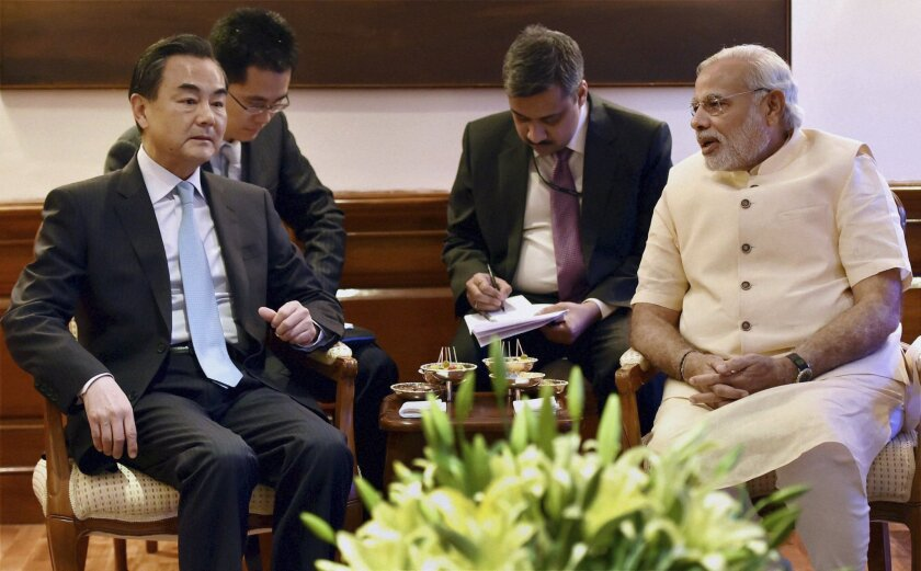 FILE - In this Monday, June 9, 2014 file photo, visiting Chinese Foreign Minister Wang Yi, left, sits with Indian Prime Minister Narendra Modi, right during their meeting in New Delhi, India. Amid fierce disputes with Japan, Vietnam and the Philippines, China is reaching out in a friendly way to India in a warming trend that could help ramp up economic exchanges and dissipate decades of distrust between the two giant neighbors. (AP Photo, File)