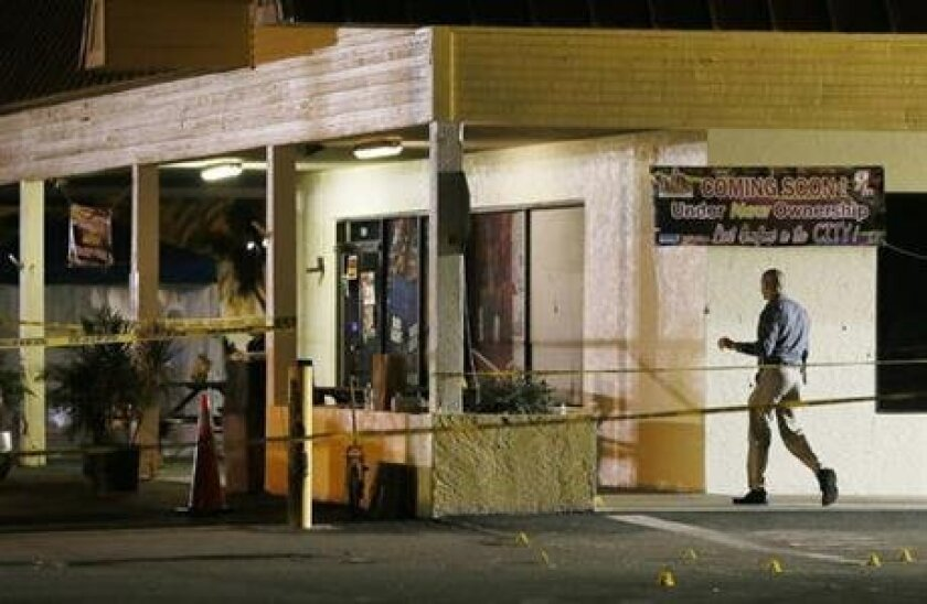 An investigator walks near the scene of a fatal shooting at Club Blu nightclub in Fort Myers, Fla., Monday, July 25, 2016. (Kinfay Moroti/The News-Press via AP)