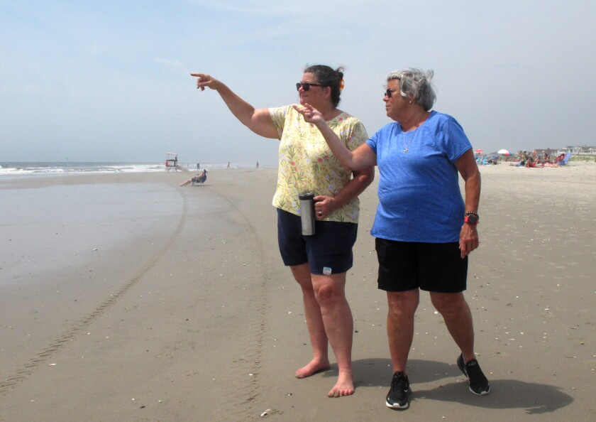 Suzanne Hornick, left, and Susan Cox, right, look out to sea from a beach in Ocean City N.J. on July 8, 2021 where power cables from an offshore wind farm are projected to come ashore. They are among opponents of offshore wind who question its impact on the ocean, the environment and the economy. (AP Photo/Wayne Parry)