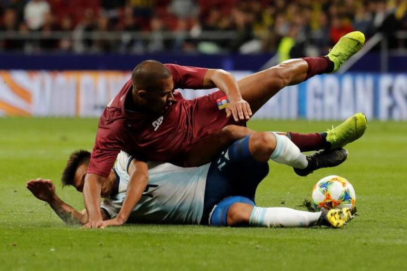 El delantero de la selección de Venezuela, José Rondón, cae ante la entrada del defensa de Argentina, Lisandro Martínez, durante el encuentro amistoso que disputaron esta noche en el estadio Wanda Metropolitano, en Madrid. EFE / Juan Carlos Hidalgo.