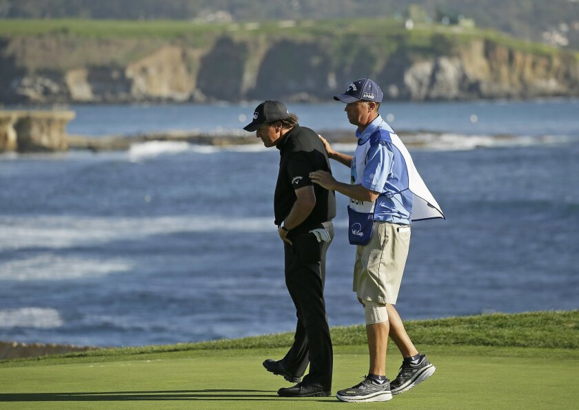 """Phil Mickelson, left, is consoled by his caddie, Jim """"Bones"""" Mackay on the 18th green of the Pebble Beach Golf Links during the final round of the AT&T Pebble Beach National Pro-Am golf tournament Sunday, Feb. 14, 2016, in Pebble Beach, Calif. Vaughn Taylor won the tournament. (AP Photo/Eric Risber"""