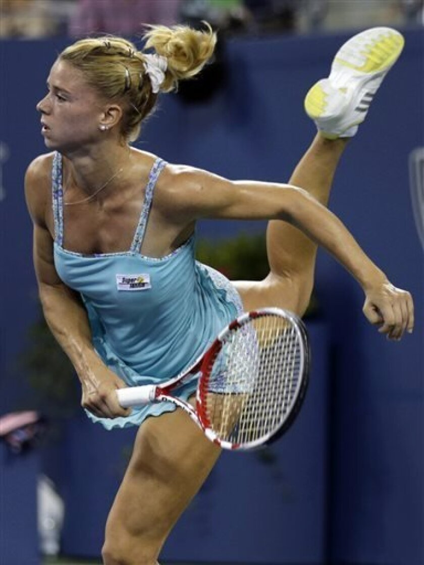 Camila Giorgi, of Italy, follows through on a serve to Caroline Wozniacki, of Denmark, during the third round of the 2013 U.S. Open tennis tournament, Saturday, Aug. 31, 2013, in New York. (AP Photo/Charles Krupa)