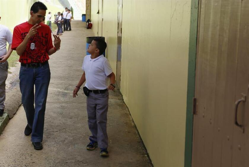 Yanluys Aponte (dcha.), un niño que lleva un implante coclear, habla en signos con su asistente Jesús Marrero, también sordo, en la escuela Ana Dalila Burgos en Orocovis, un pueblo en el centro geográfico de Puerto Rico. EFE/Archivo
